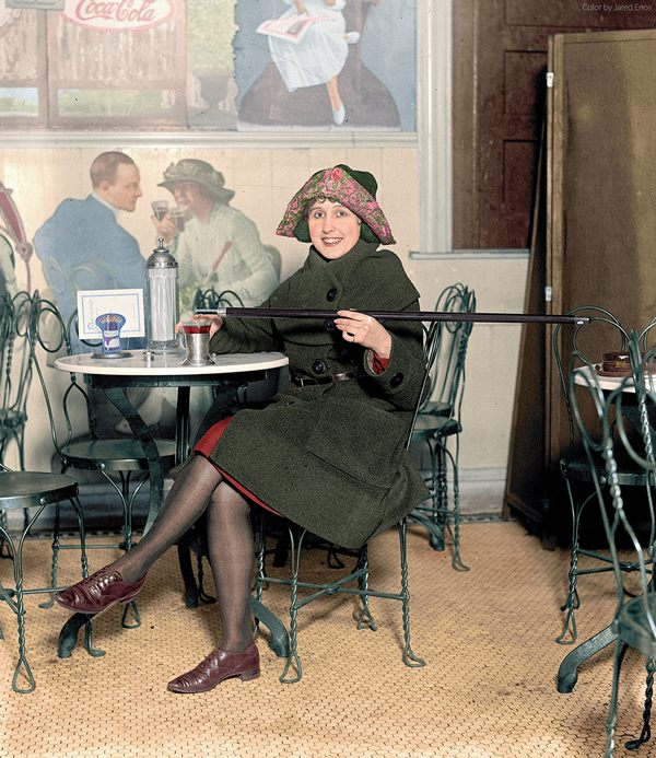 Woman seated at a soda fountain table is pouring alcohol into a cup from a cane, during Prohibition; with a large Coca-Cola advertisement on the wall